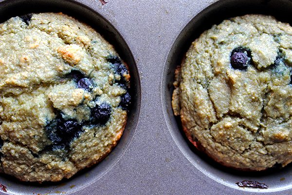 Two muffins with blueberries in tray