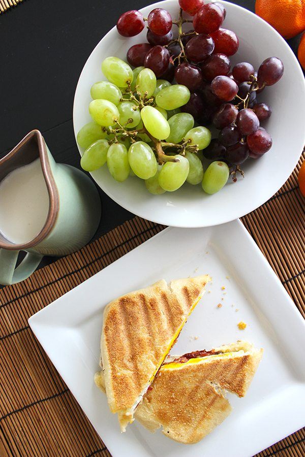 egg, cheese and bacon on bread with grapes on the side