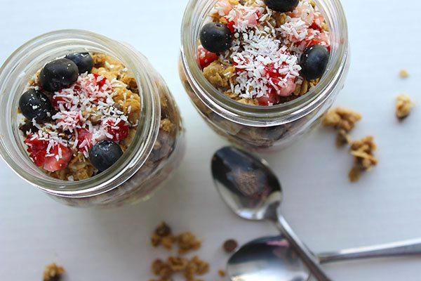 Two mason jars filled with yogurt and fruit