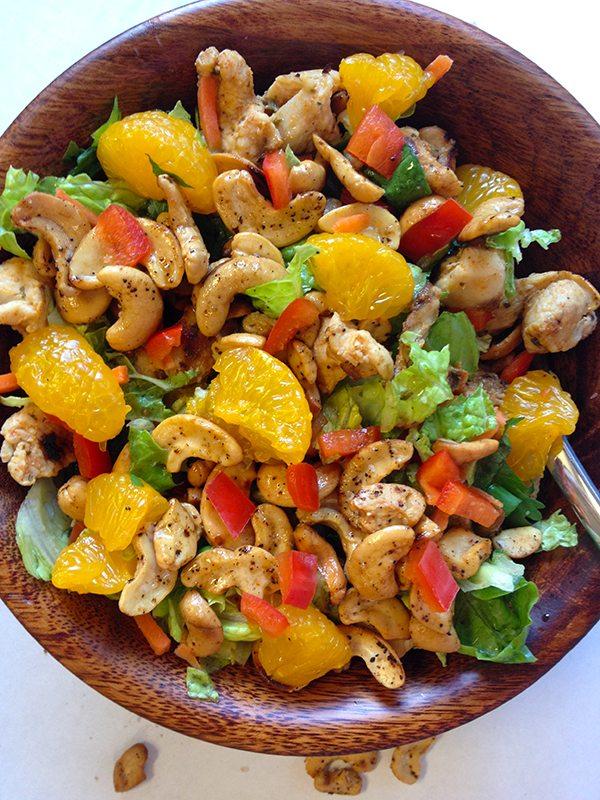 Chicken, lettuce, orange and nut salad in wooden bowl