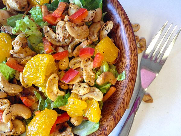 wooden bowl filled with lettuce, chicken, cashews and oranges next to fork