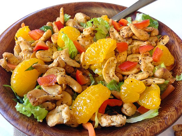 Chicken salad with nuts and oranges in bowl