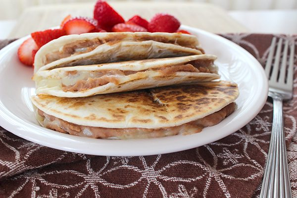 cheese quesadillas with pinto beans on white plate with strawberries