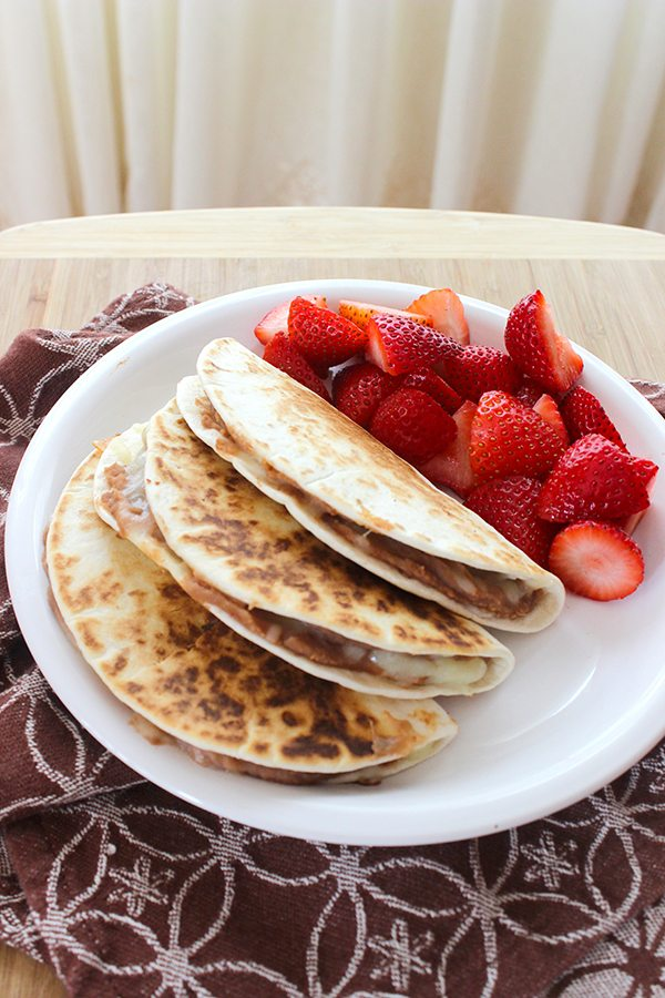 close up white plate of three stuffed tortillas with strawberries