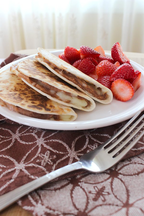 quesadillas con queso on white plate with strawberries