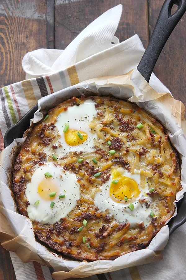 Sunny side eggs, sausage and hash browns in skillet