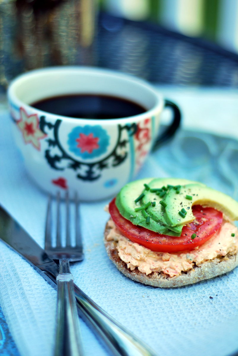 Avocado slices, tomato and vegetable cream cheese on toast with coffee