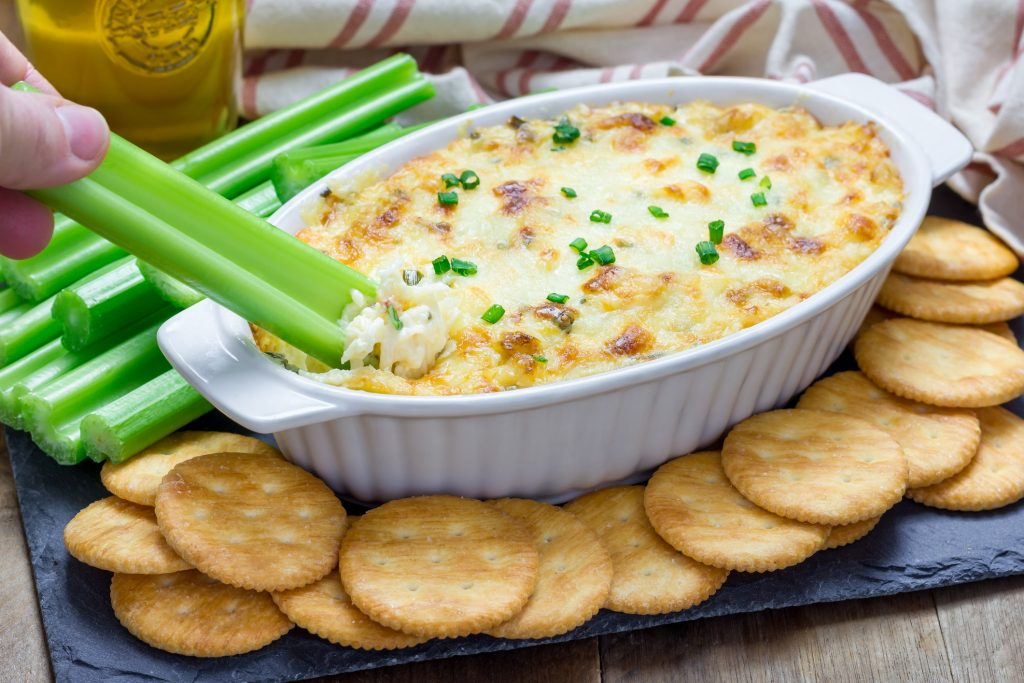 crab dip in white bowl next to crackers and celery sticks