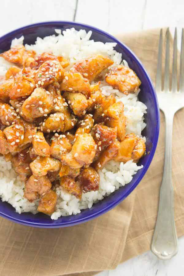 Chicken coated with sesame seeds and honey on top of rice