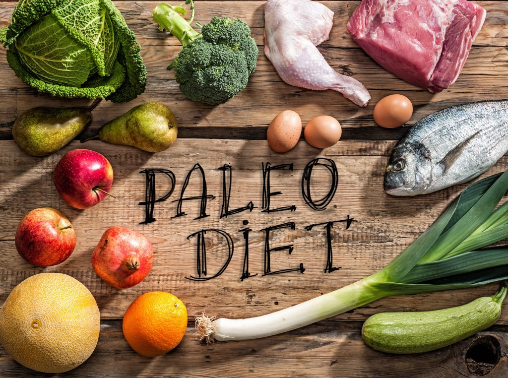 Paleo diet meat, fish,eggs and vegetables on wood counter