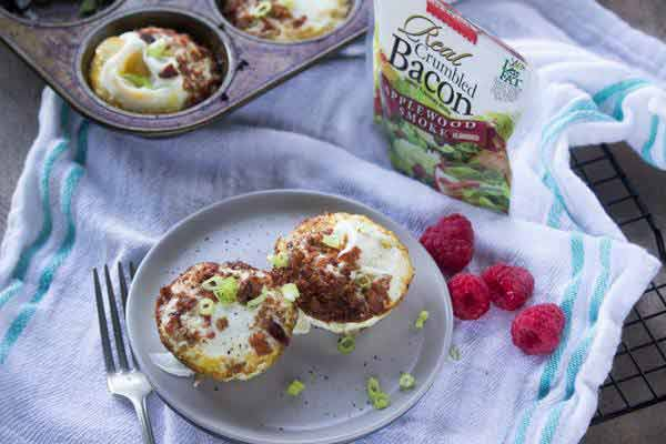 Two bacon egg and green onion muffins on plate