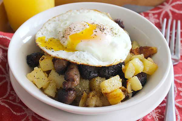 Sausage, egg and potato breakfast in a white bowl