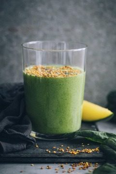Spinach Smoothie in tall glass with bee pollen on top