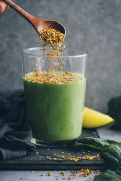 Green Spinach Smoothie in a glass with bee polleen added on top