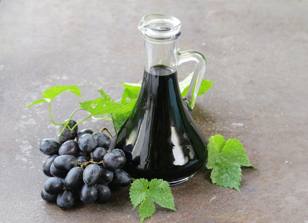 best balsamic vinegar in glass carafe surrounded by grapes