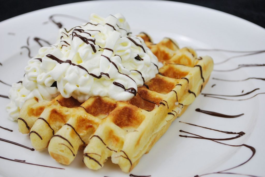 belgian waffle with whipped cream on plate