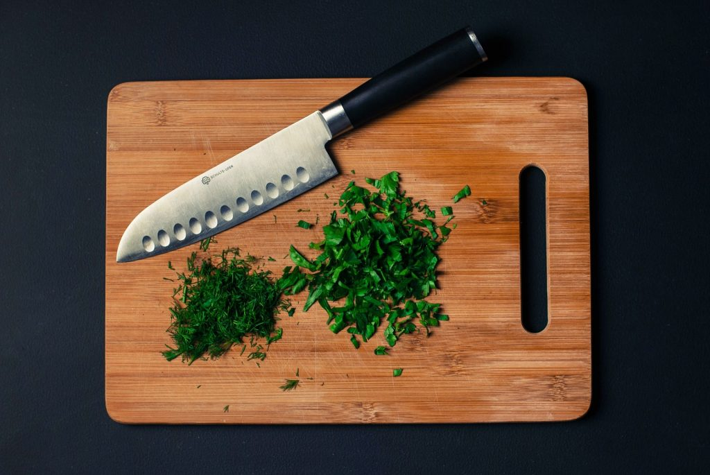 best chef knife under 100 on cutting board with diced herbs