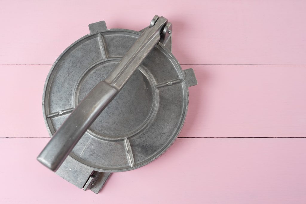 authentic tortilla press isolated on pink wood table