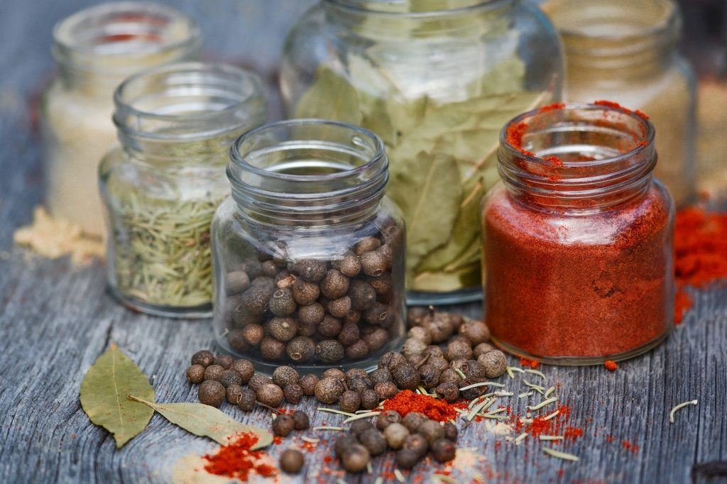Spices in small glass jars on wood countertop
