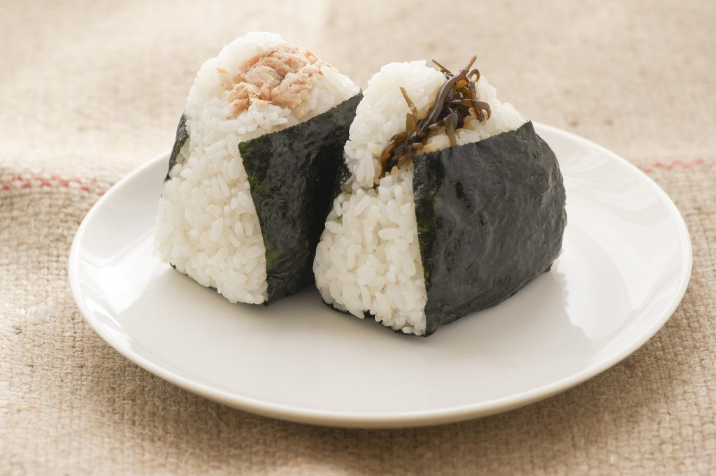 two japanese rice balls wrapped in seaweed