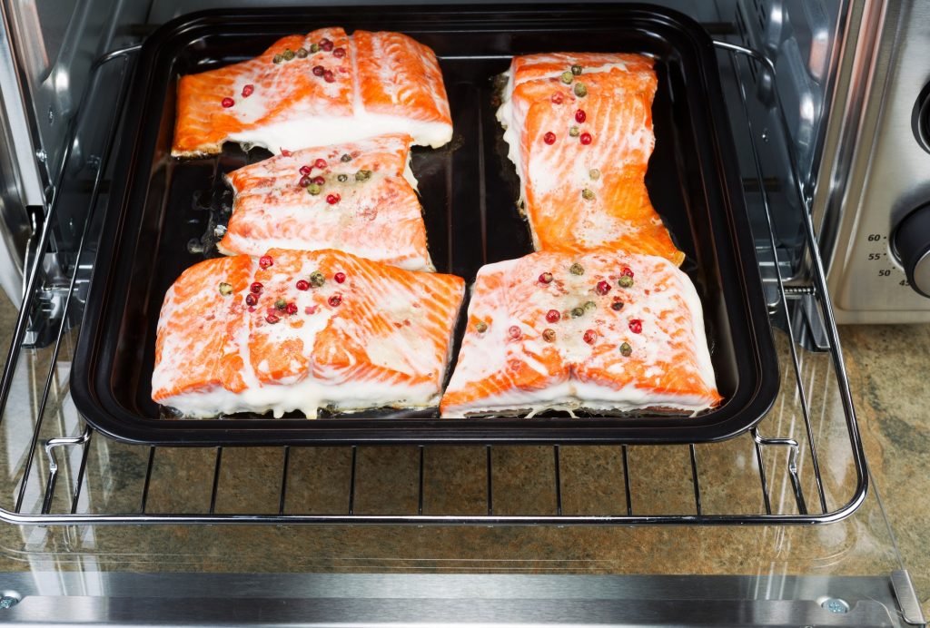 large countertop convection oven with baked salmon fillets inside