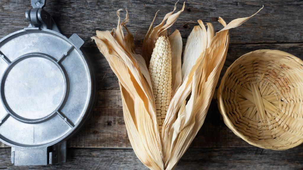 tortilla presser next to dry corn stalk and straw basket on wooden background