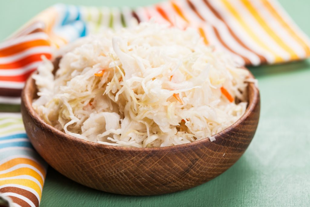 sauerkraut in a wooden bowl on the table next to colorful napkin
