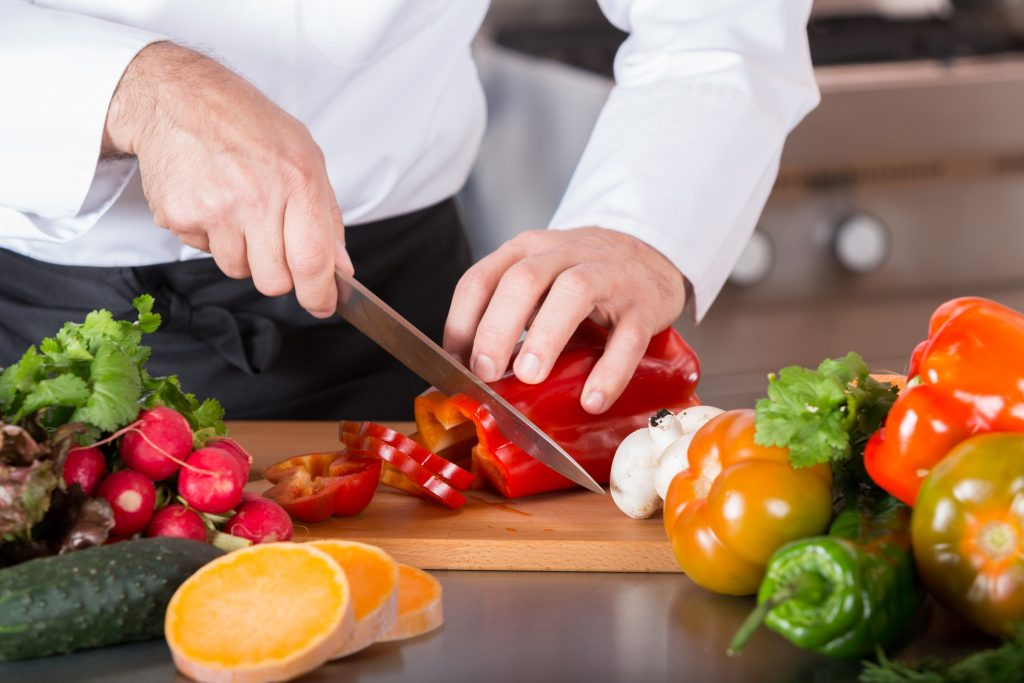 professional chef slicing a red pepper with a good chef knife