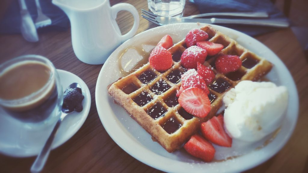 waffle with syrup and strawberries on plate