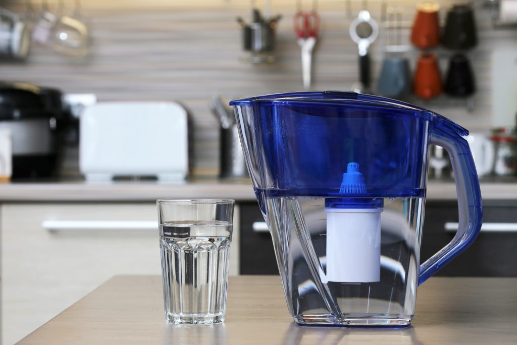 pitcher water filter near glass of water on kitchen table