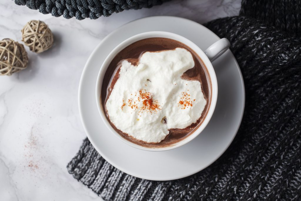 hot chocolate french style topped with whipped cream on marble table