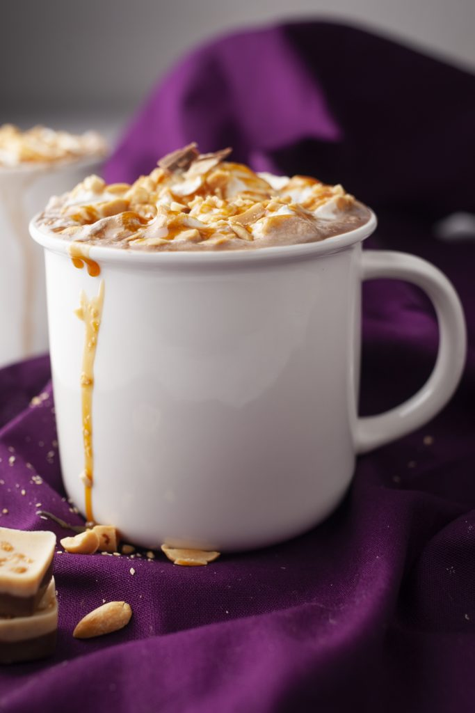 White mug filled with hot chocolate, whipped cream and caramel