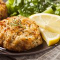 crab cakes on plate with sliced lemons