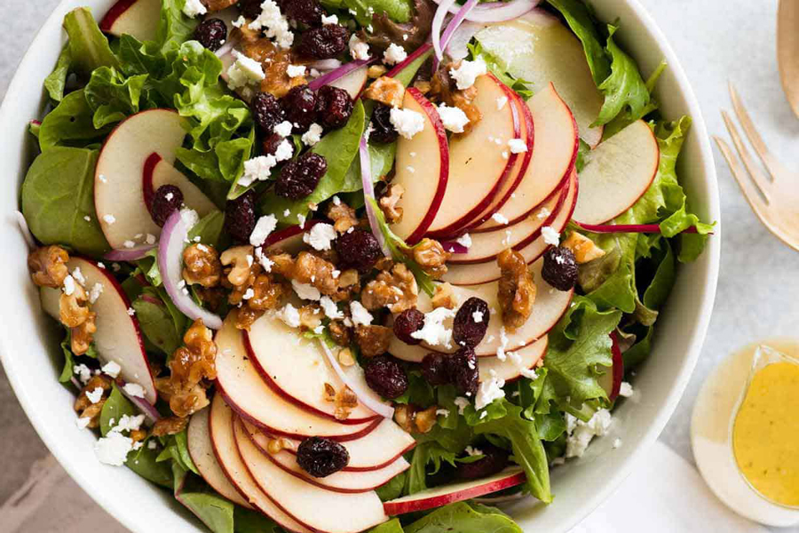 Apple Salad with Candied Walnuts and Cranberries in bowl