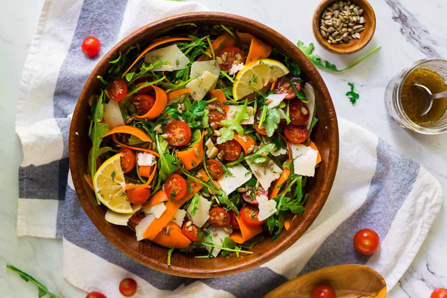 Wooden bowl of arugula salad with tomatoes, carrots, and Parmesan cheese