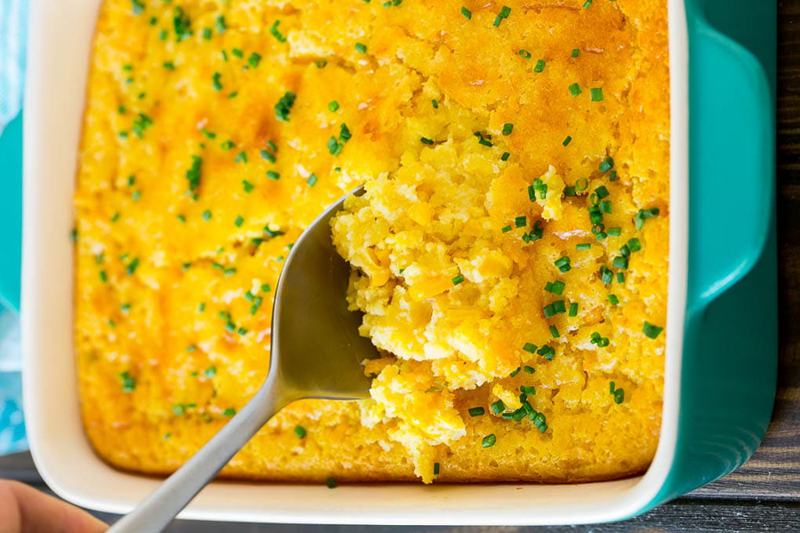 Pan of corn pudding with a serving spoon in it.