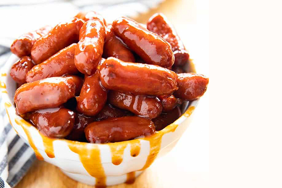 BBQ mini hot dogs in white bowl on wood table