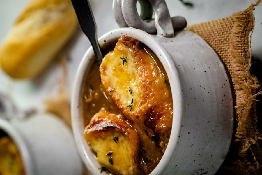 french onion soup in white bowl with bread