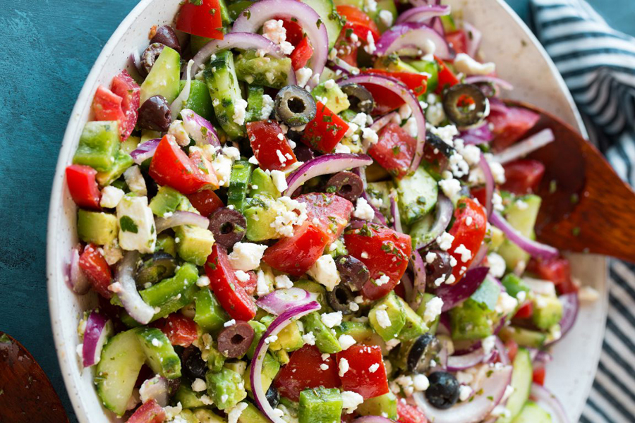 greek salad in white bowl with wooden spoon