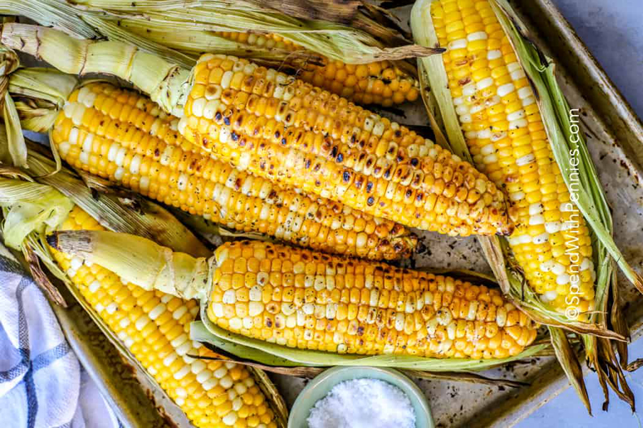 Grilled corn on the cob shown on a baking tray with salt