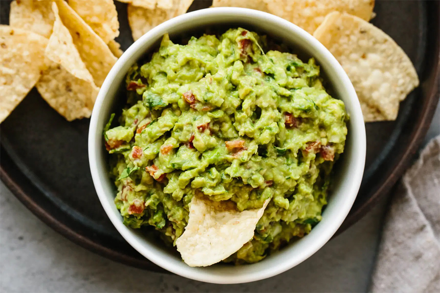 Guacamole in a bowl with a chip dipping in.
