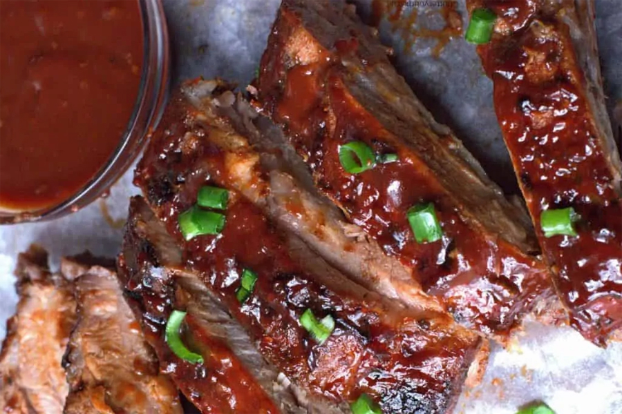 Sliced BBQ baked ribs with dipping sauce