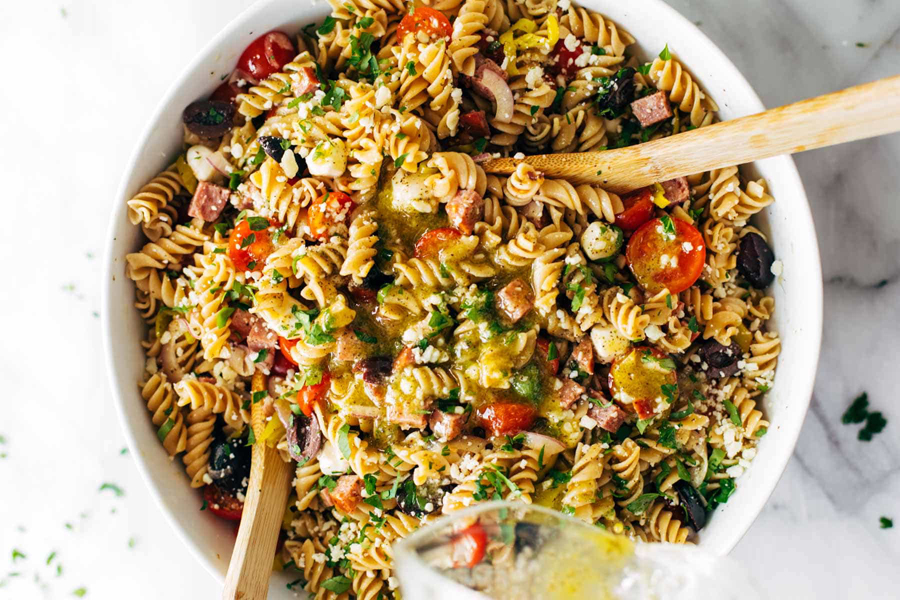 Pasta salad in bowl with spoons.