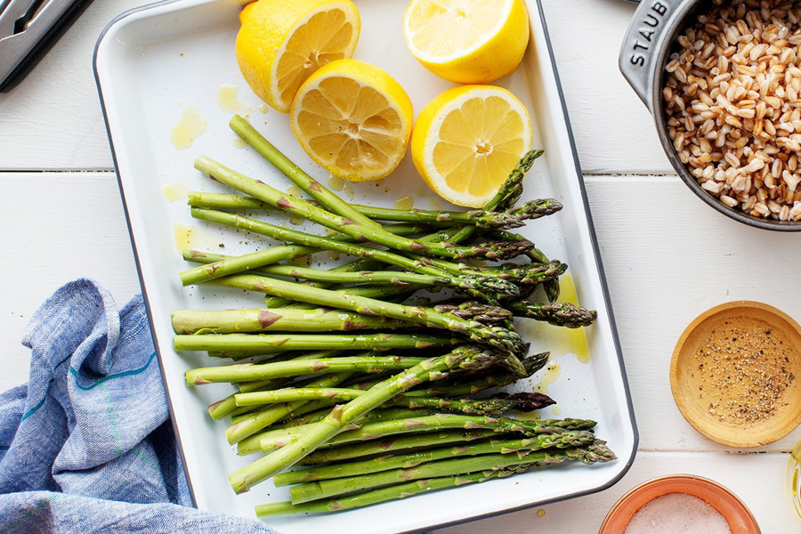 Cooked asparagus with lemons in white pan