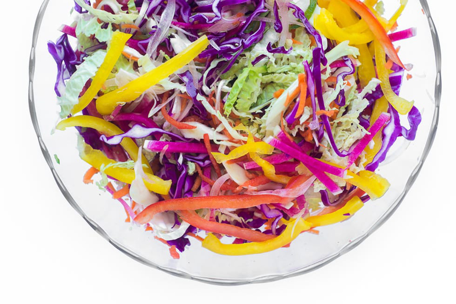 Spicy rainbow slaw in clear glass bowl