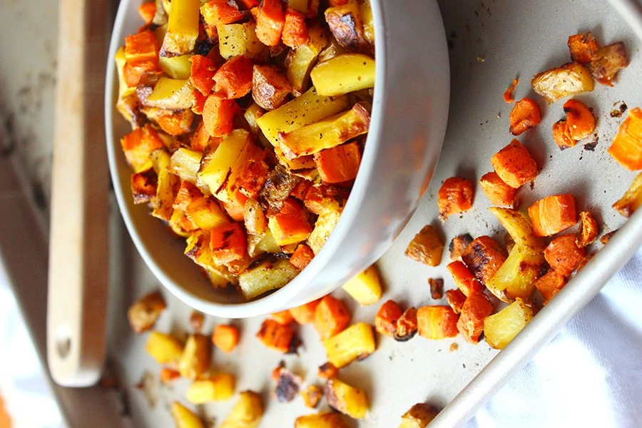 Roasted Carrots and Potatoes in bowl on a sheet pan