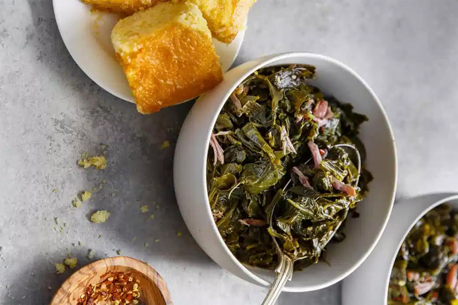 collard greens in white bowl with spoon