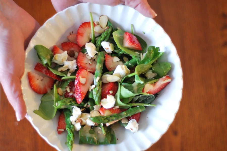 spinach,asparagus and strawberry salad in white bowl