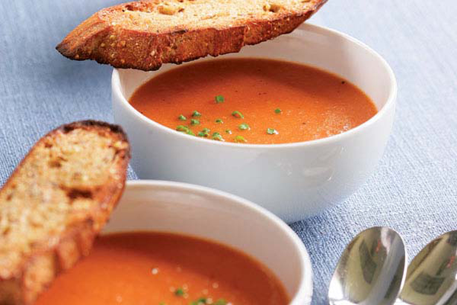 two white bowls filled with tomato soup
