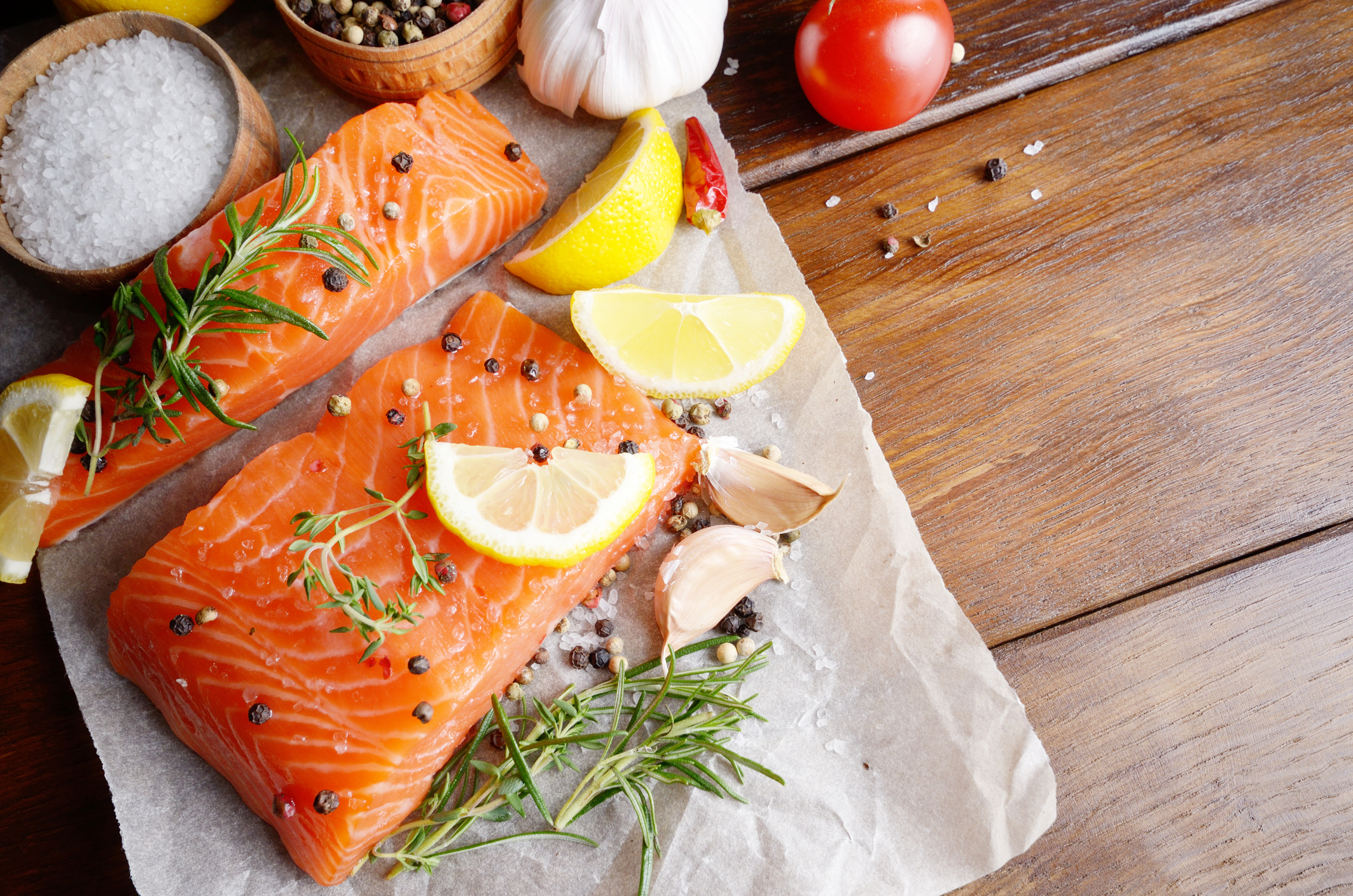 two raw salmon fillets with lemon on parchment paper
